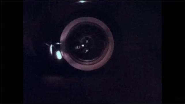 1960s: Light spins on rear tire of car. Car drives along pavement at dusk. Light rotates on rear car tire.
