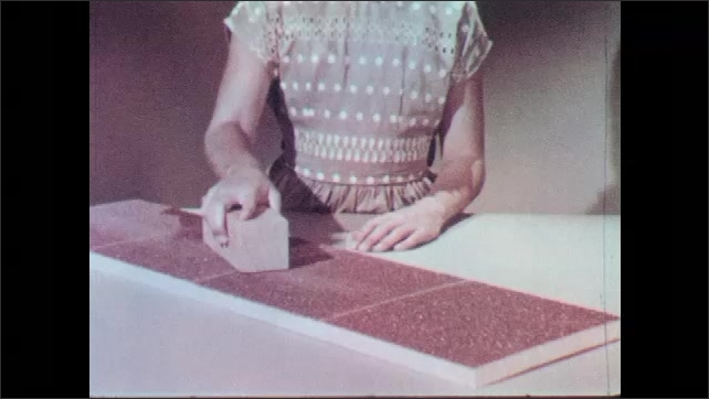 1960s: Text appears over convertible in street. Girl pushes wooden block along large piece of sand paper. Hand reveals sandpaper on bottom of wooden block.