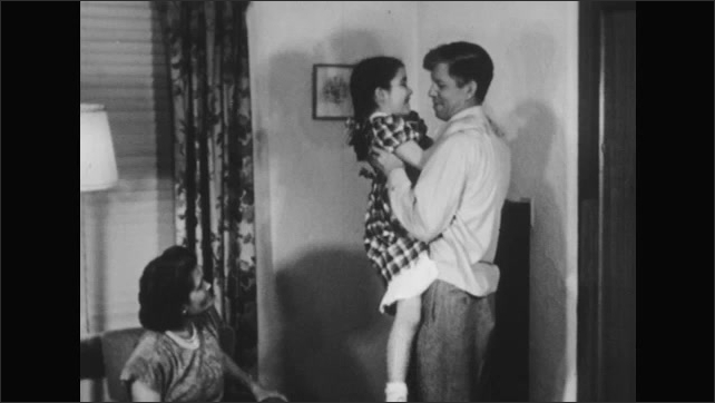 1950s: Man stands in living room holding girl, talking to her. Man sets girl down. Woman stands up from chair and walks with girl out of room.
