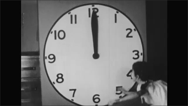 1950s: Pie sits on floor cut into quarters. Girl points at the four quarters of pie. Girl stands up to painting of large clock in bedroom and moves minute hand all the way around clock from 12 to 12.