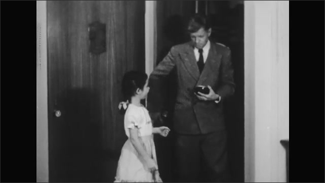1950s: Man and girl stand together at closet door in house. Man pull clock from closet and hands it to girl. Girl holding clock.