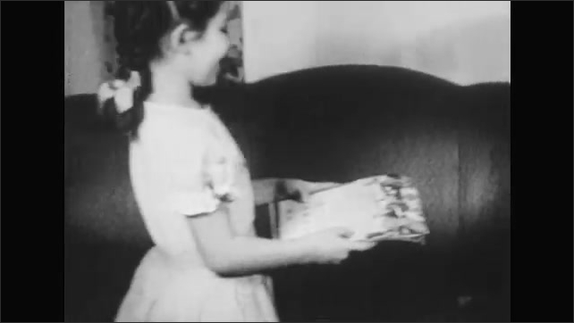 1950s: Man and girl sit on couch next to each other, talking. Girl holds clock and hands it to man. Girl gets up and comes back with calendar. Girl points to dates in calendar.