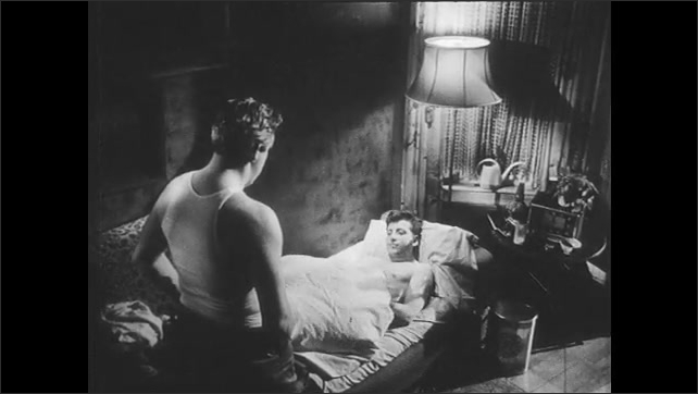1960s: Men speak.  Man stands.  Young man takes drink and lays down on bed.  Father covers son with blanket.