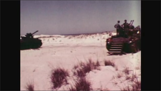 1970s: UNITED STATES: RCAT in sky. Tanks take position on sand. Tanks prepare to shoot object in sky