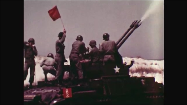 1970s: UNITED STATES: men stand on M42 tank roof. Tank fires at object in sky. Man holds up red flag. Ground based pilot flies model plane