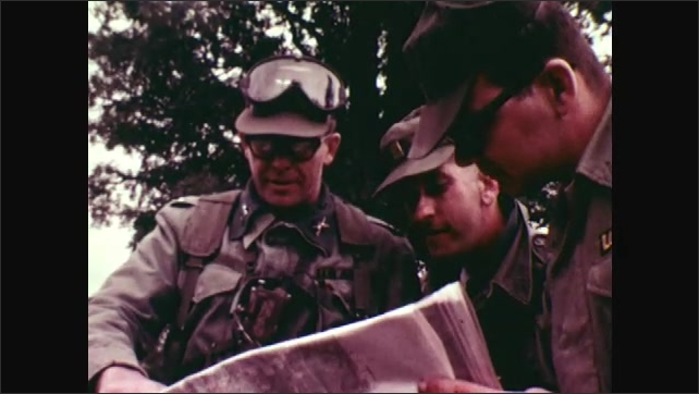 1970s: UNITED STATES: Michigan camp and guard on training exercise. Soldier with safety goggles. Men look at charts