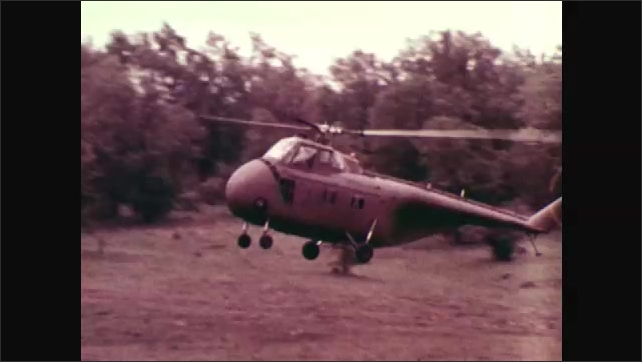 1970s: UNITED STATES: Battle planning strategy. Helicopter lands in forest.