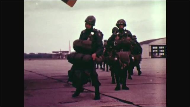 1970s: UNITED STATES: Air force plane on runway. Soldiers line up by plane. West Virginia Guardsman. Soldier carries heavy pack.
