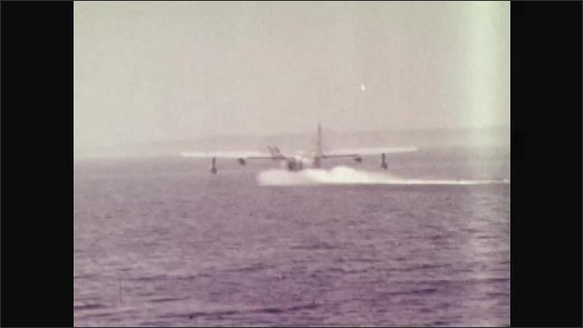 1970s: UNITED STATES: Amphibian aircraft lands on sea. Flying boat. Plane lands by boat on sea