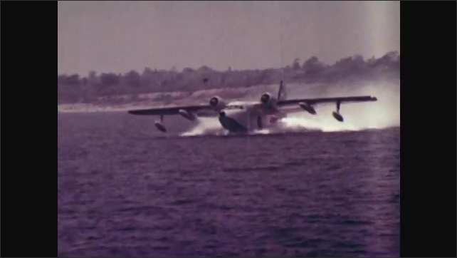 1970s: UNITED STATES: Flying boat lands on water. Amphibian plane takes off from sea. Plane flies across water.