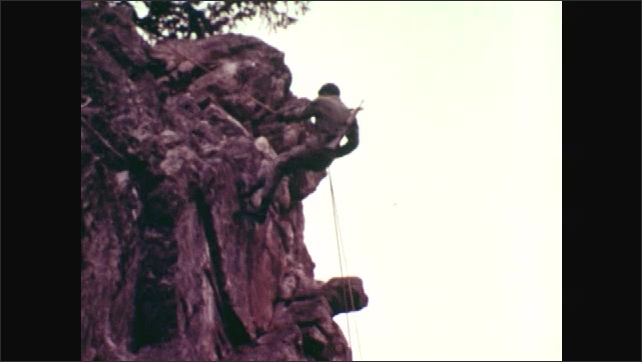 1970s: UNITED STATES: rock face in mountains. Soldier abseils down cliff face