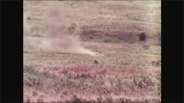 1970s: Soldier looks through binoculars. Soldiers shoots large caliber gun from back of jeep. Explosion. Radar station.