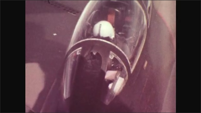 1970s: Refueling pipe connected to plane, pilot in cockpit of plane. Plane refuels in the sky.