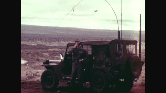 1970s: Smoke and dirt flare up from ground. Plane flies across sky. Man stands next to jeep, talks into radio. Plane drops bombs onto ground. Explosion.