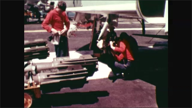 1970s: Aircraft carrier moves through ocean. Men work on airplanes.