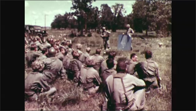 1970s: Helicopters fly away. Soldiers sit on ground, listen to men talk. Soldiers march.