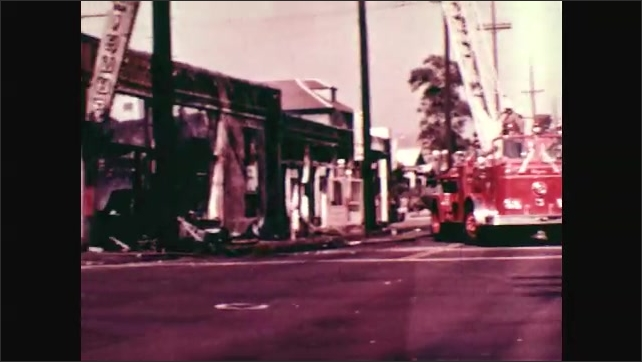 1970s: Driving down road where military soldiers are marching. Firetruck sits in intersection next to burned out building. Firefighter crosses street to burned out building.