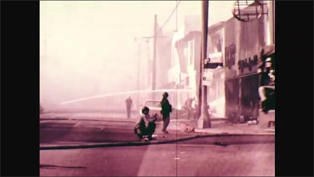 1970s: Firefighters spray burned out building with hose. Military truck with soldiers in back drives down road passed destroyed buildings.