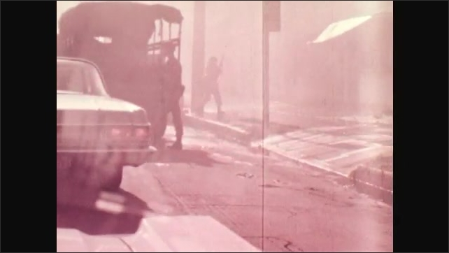 1970s: Soldiers cross street as smoke feels air. Armed soldiers sit in vehicles. Man climbs firetruck ladder.