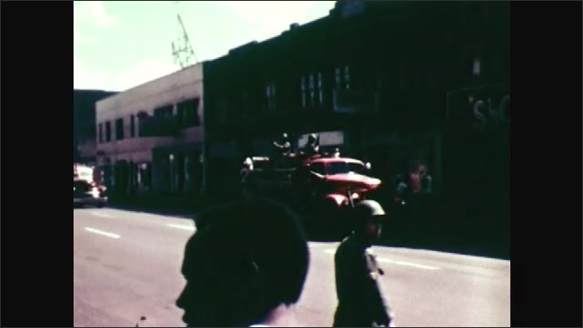 1970s: Tanks drive down road, cars follow them. People stand outside destroyed building. Firetruck drives down road. Soldier stands holding rifle.