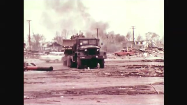 1970s: Soldiers dig through rubble of destroyed building. Soldier sawing fallen tree. Military jeep hauls equipment. Soldier in front of burning fire.