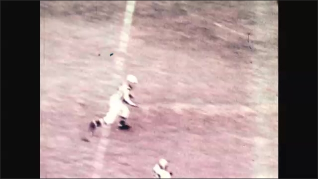 1970s: Football players playing game. Quarterback throws ball to receiver who runs ball to endzone.