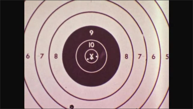 1970s: Man looks down sight of rifle. Target. Man looks down sight of gun and fires.