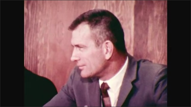 1970s: Men floating weightless in back of plane. Donald K. Slayton sits behind table being asked questions.