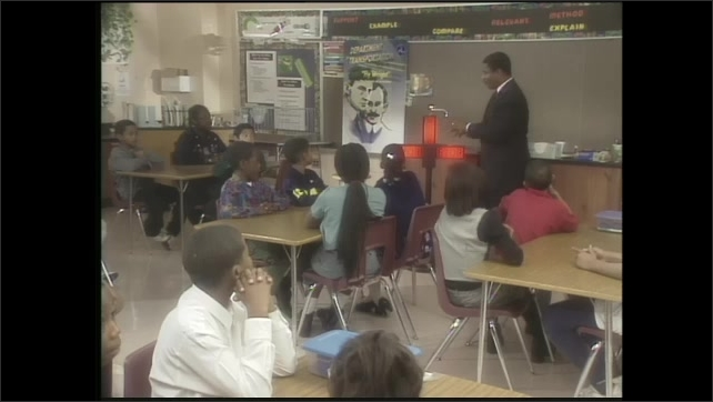 2000s: traffic light turns from red to green, cars drive through intersection, teacher stands, talks and gestures in front of classroom with seated students