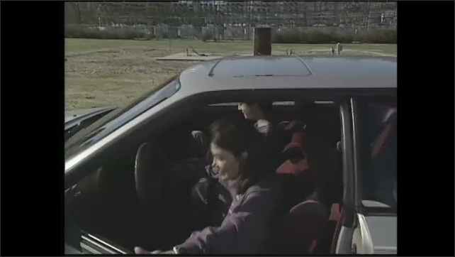 2000s: man walks away from woman and boy, woman talks as she opens car door, boy gets into car, woman gets into car with NASA logo, woman starts car, boy and woman put on seatbelts, car drives off