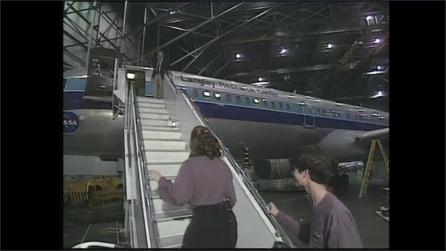 2000s: car passes traffic cones, NASA sign, woman and boy walk inside hangar to jet plane, woman waves, talks, man waves them up, woman and boy climb steps, man introduces them to man inside plane