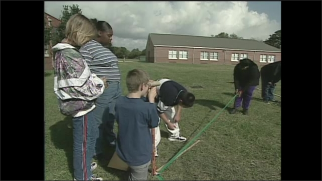 2000s: students outside school, boy raises hand, looking through tube at kneeling boy, boy marks yardstick near tape, students measure, unroll tape, students on grass gather, wave, jump