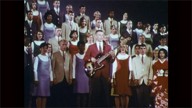 1960s: Man in red suit stands on stage, plays the guitar and sings, behind him stands a choir and sings.
