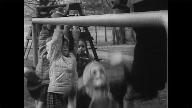 1960s: School playground, boy flips upside down on jungle gym, children in winter coats hang from monkey bars. Girl waves to man in school window, holds up doll. Man waves, shuts window.
