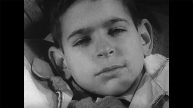 1960s: Living room, mother nods, talks, boy talks, mother wipes tears away, mother shakes head. Children walk along sidewalk by school.