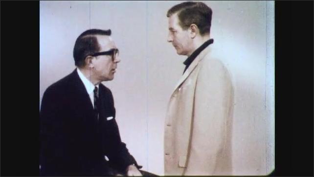 1960s: Man shakes head, talks. Man sits across from man, talks. Man walks over to man, sits down, men talk.