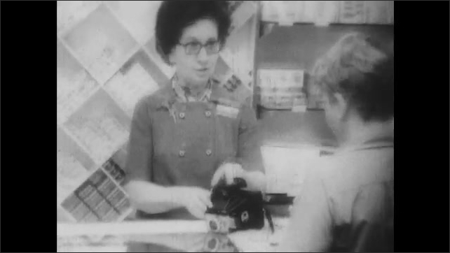 1970s: A boy looks at a camera in the store, helped by a sales lady. Another sales lady helps a girl try a wig on.