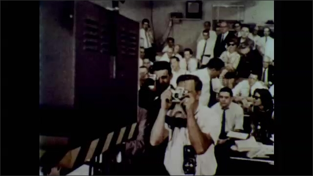 1960s: Satellite across night sky. U.S. flag on two monitors. Men in headsets watch tv with flag. Man takes photograph of tv. Two men watch tv with flag. Illustration of satellite in Earth's orbit.