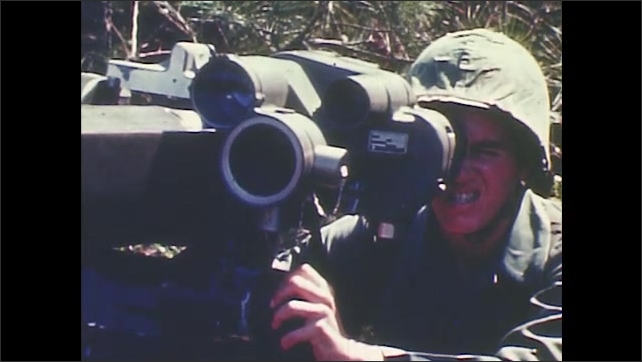 1960s: Soldier looks through binoculars. Soldier looks through gun sight. Soldiers stand by rocket launcher in the forest. Smoke from explosion. Soldier fires machine gun from the ground.