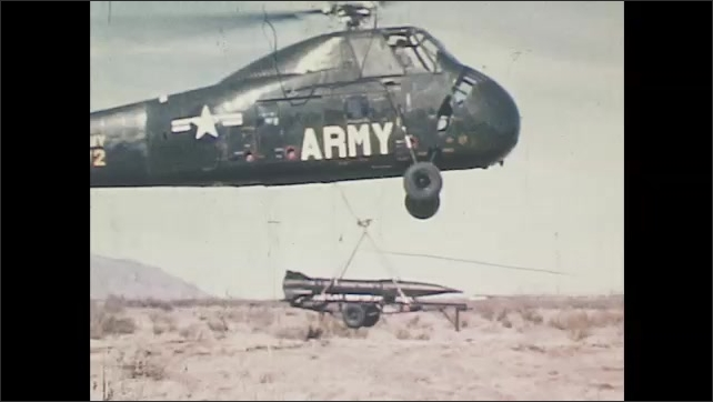 1960s: Military hybrid vehicle drives over land and water. Army helicopter drops a missile in the desert. Soldiers carry missile on wheels from helicopter. Helicopter flies with missiles.