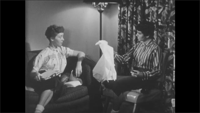 1950s: Teenage girls speak.  Girl works on and holds up sewing project.  Girl leans in.  Girl holds clipboard.