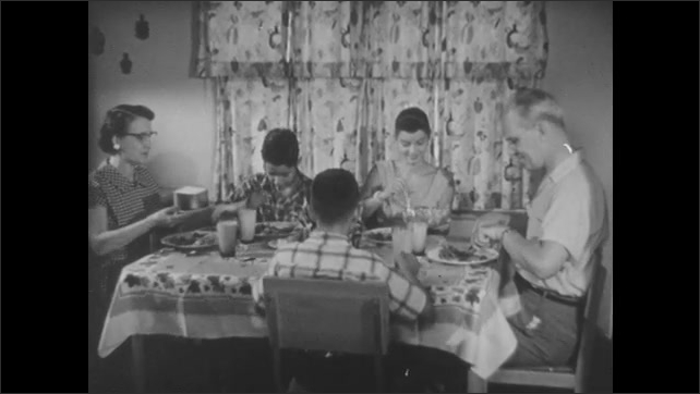 1950s: Woman selects meat at butcher shop.  Woman puts food in freezer.  Family eats meal.  Woman passes bread.  Teacher points at chalkboard and speaks.  Male and female students watch.