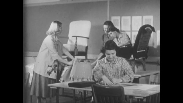1950s: Woman hangs curtains.  Girls work in workshop.  Girls lay fabric over chair.