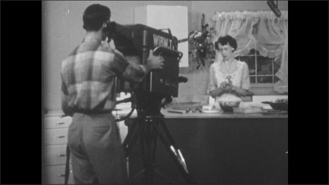 1950s: People work in office.  Woman types.  Television show set.  Woman cooks and speaks.  Teacher and student talk at desk.