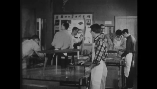 1950s: Man wearing glasses in shop class. Students in shop class. Man at work in class. Teacher approaches student.