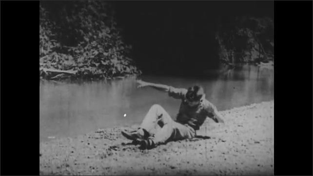 1940s: UNITED STATES: boys sleeps on ground by river. Boy gets up from ground.