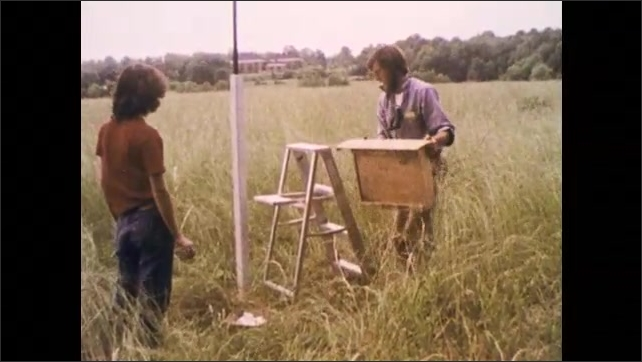 1970s: Man descends ladder against stripped tree. Baby bird and eggs in palm of hand. Man stands on step-ladder to refill nest box in field as woman watches.
