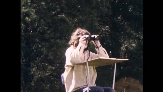 1970s: Man with binoculars. Man takes bird from nest box in field. Woman examines. Hand holds bird. Woman on ladder looks in binoculars, records findings. Woman opens box containing Super 8mm camera.