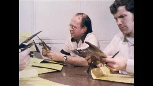 1970s: Man sort through folders. Biologists look at bird wings in folders, mark classification.