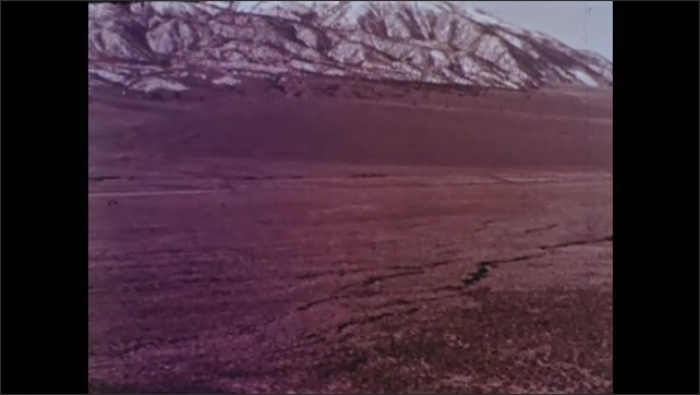 1960s: UNITED STATES: hurricane force winds blow trees. View along valley by mountains. Boy fixes flat tyre on bike.